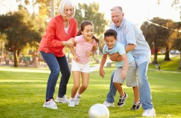 Image of senior couple playing ball with grandchildren
